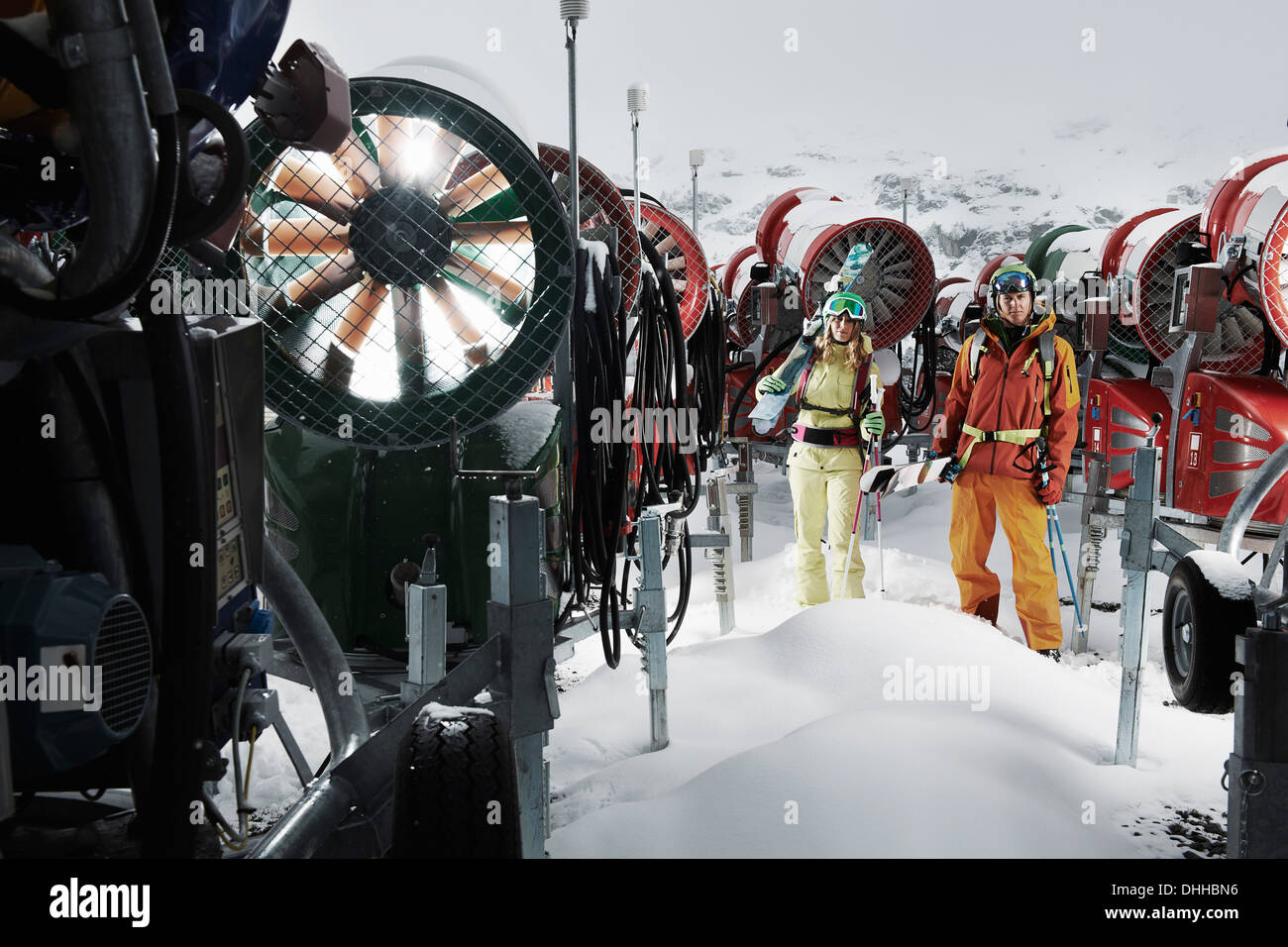 Young people standing among snowmobiles - Stock Image