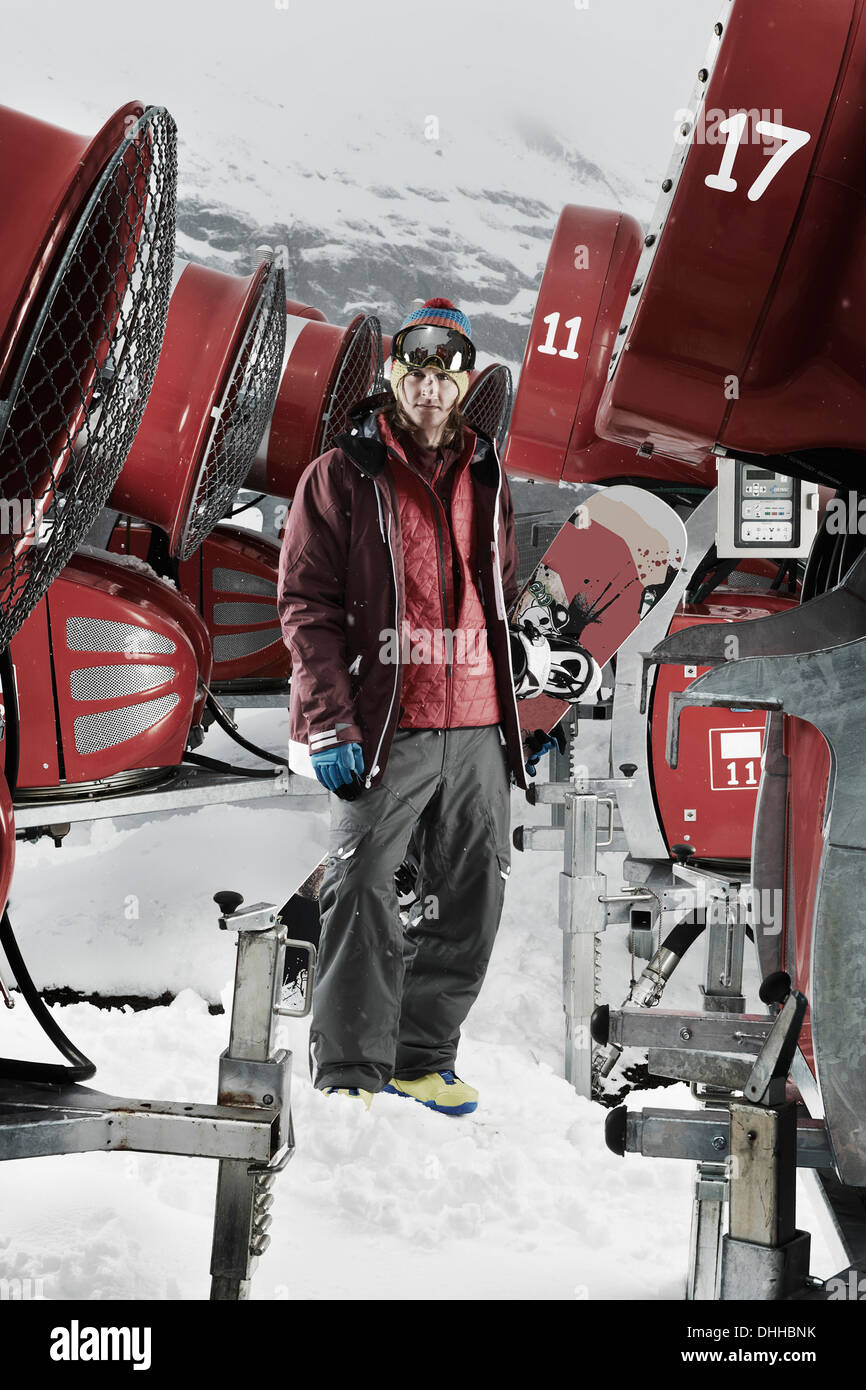 Young man standing among snowmobiles - Stock Image