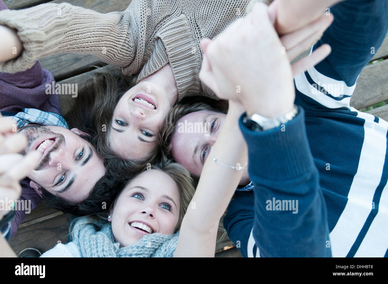 Group of four friends with heads together - Stock Image