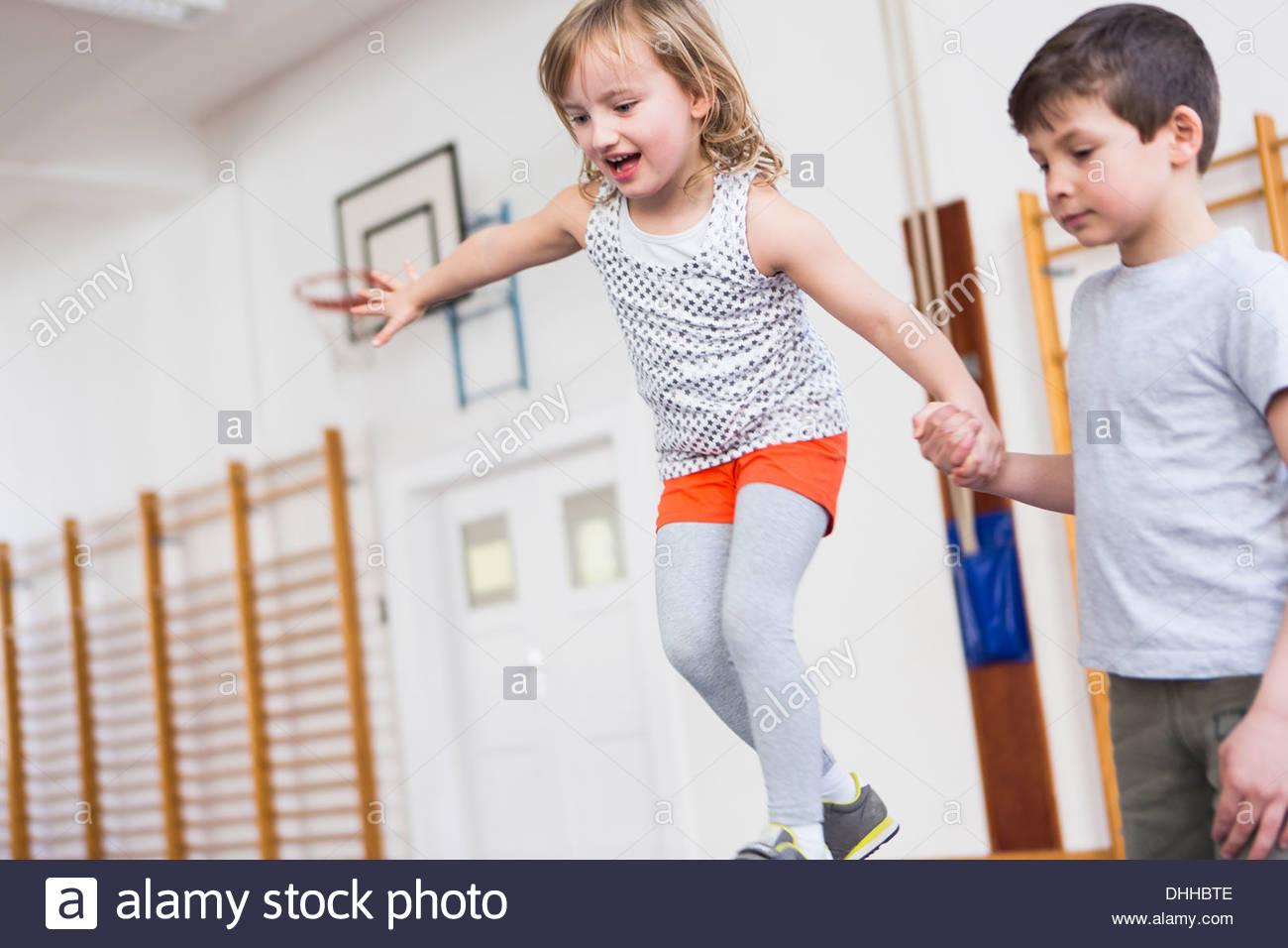 Boy holding girl's hand as she walks across balance beam - Stock Image