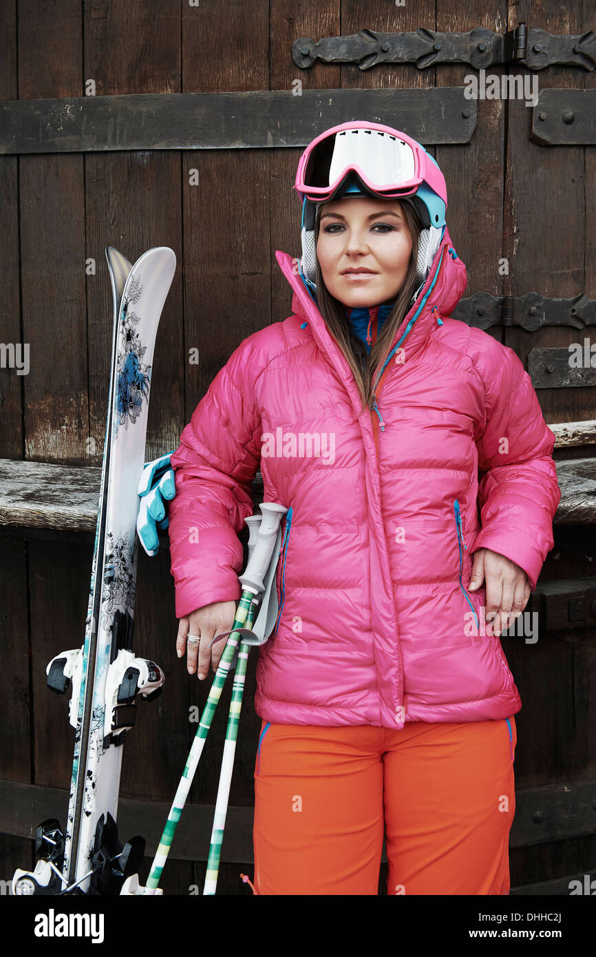 Young woman leaning against door, wearing skiwear and carrying ski equipment - Stock Image