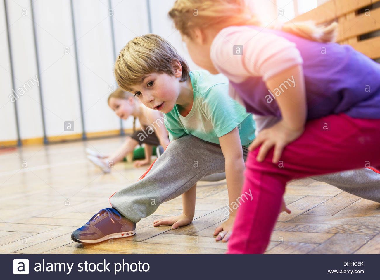 Children stretching, legs bent, leaning forwards - Stock Image