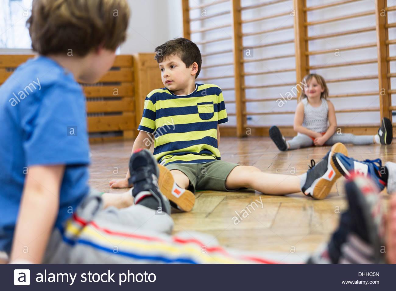 Children sitting on wooden floor, legs apart - Stock Image