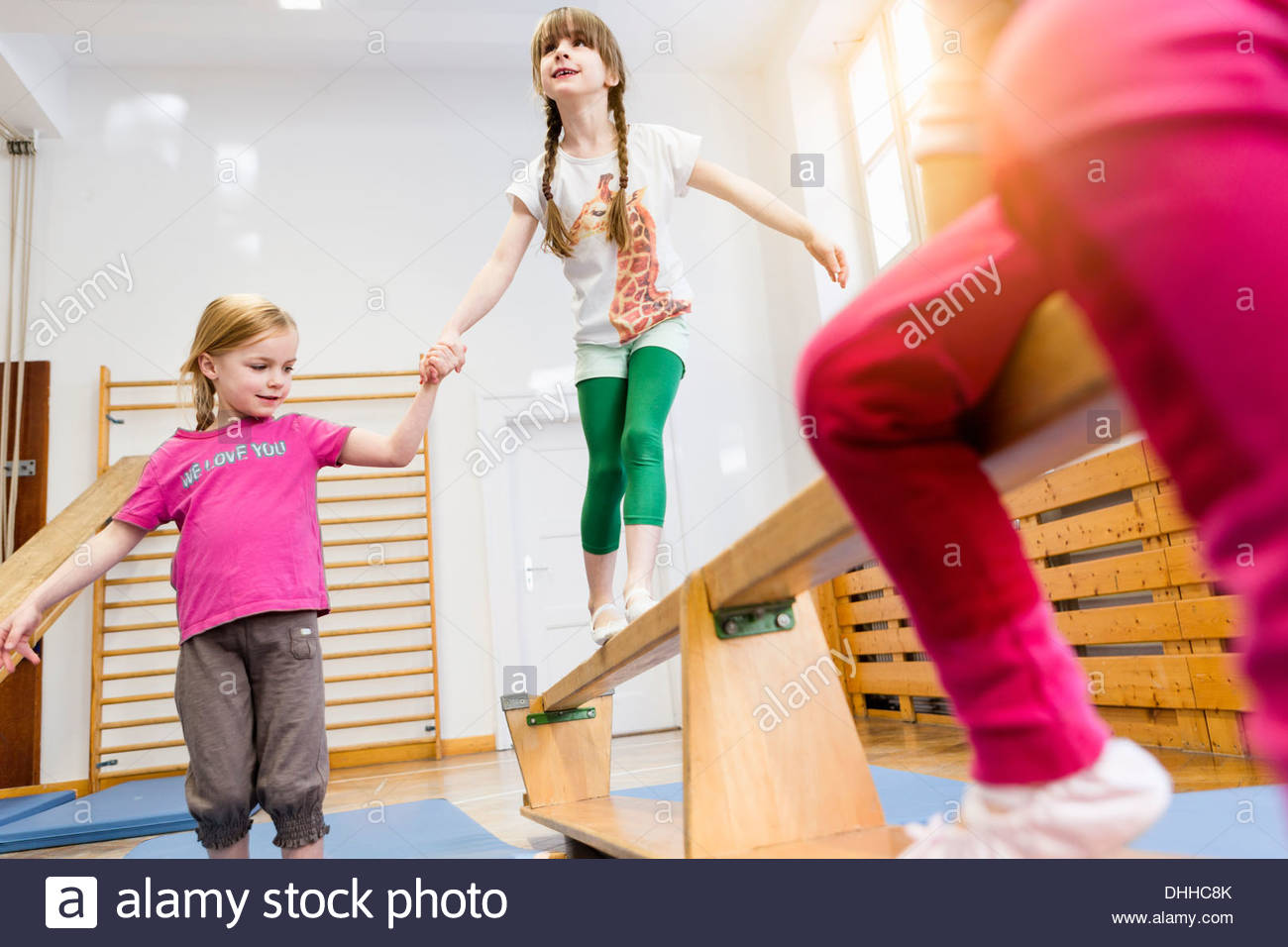 Girl holding hands helping friend across balance beam, friend in foreground - Stock Image