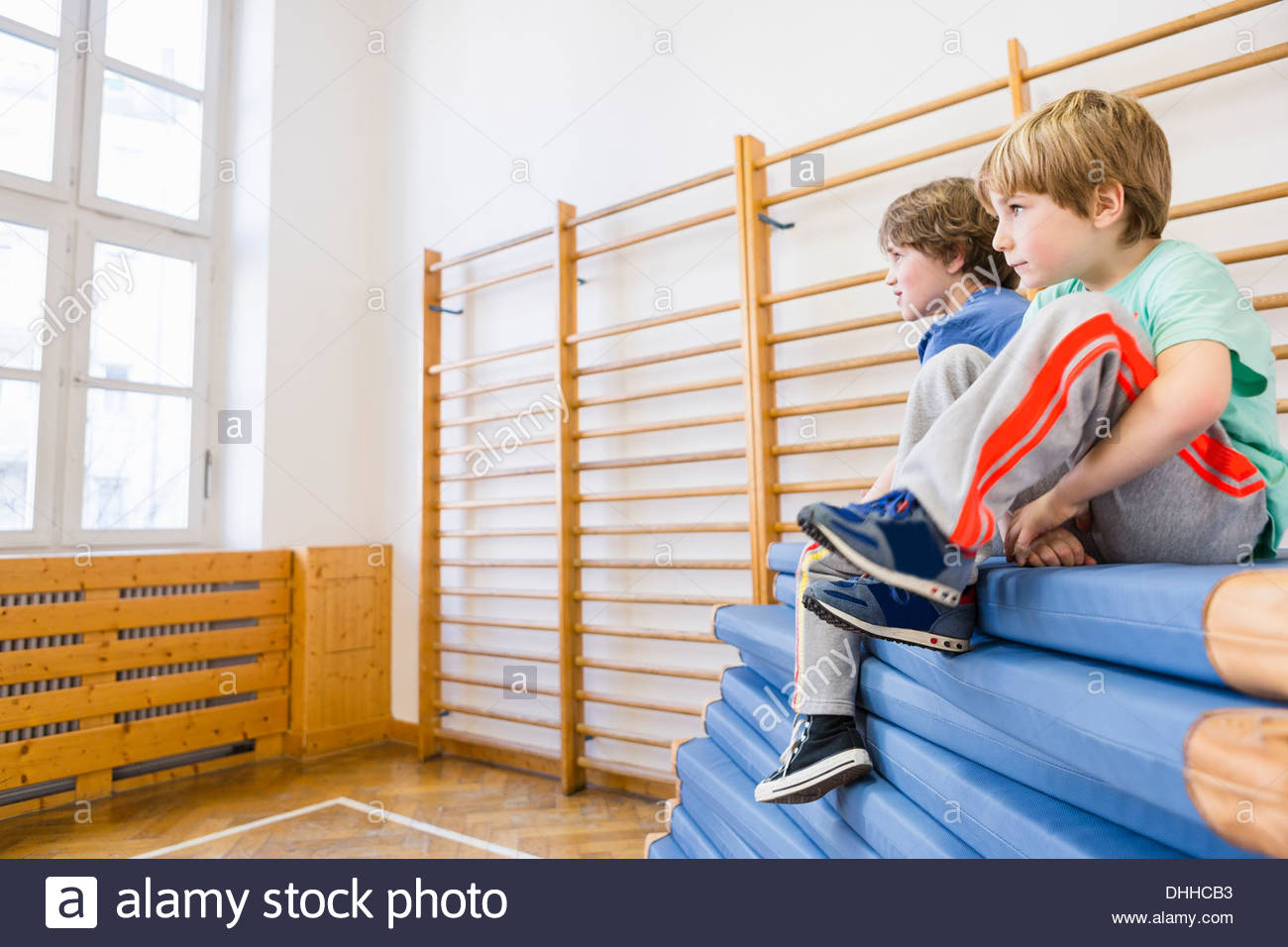 Boys sitting on top of pile of blue exercise mats - Stock Image