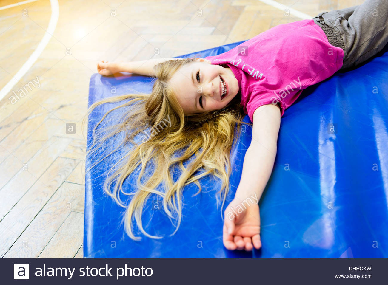 Girl lying on blue exercise mat, smiling - Stock Image