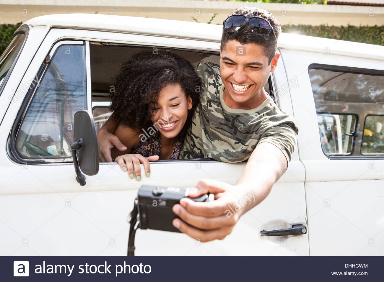 Couple taking photograph from inside van - Stock Image
