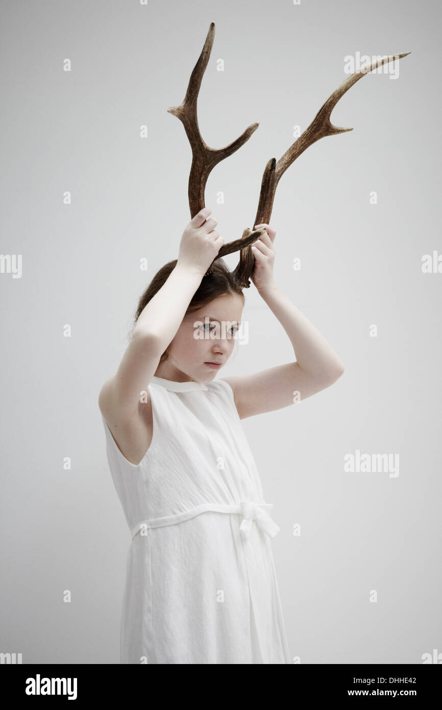 Girl posing with antlers on head - Stock Image