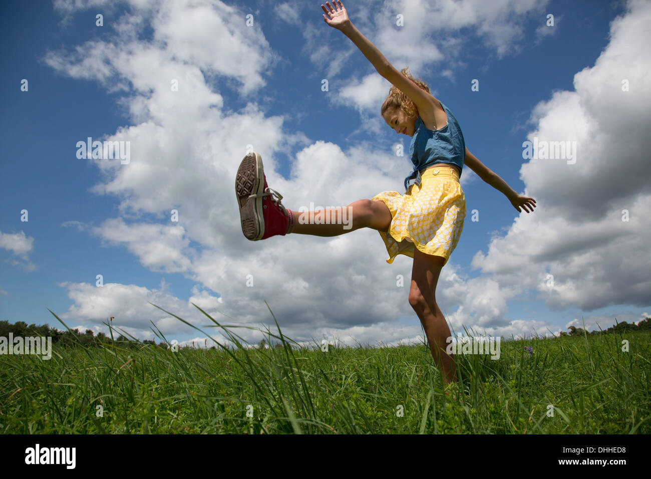Teenage girl kicking leg in field - Stock Image