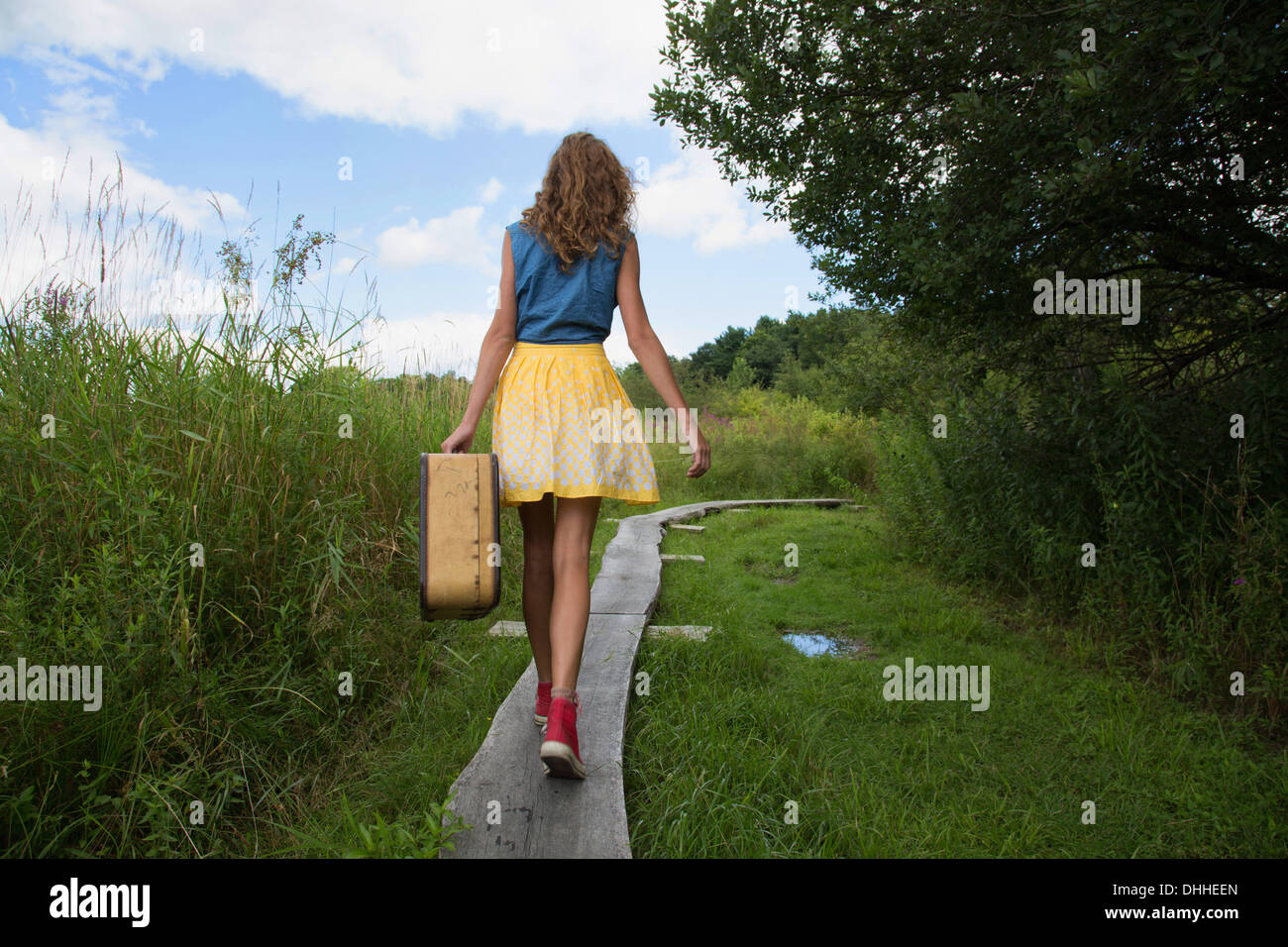 Teenage girl carrying suitcase on rural path - Stock Image