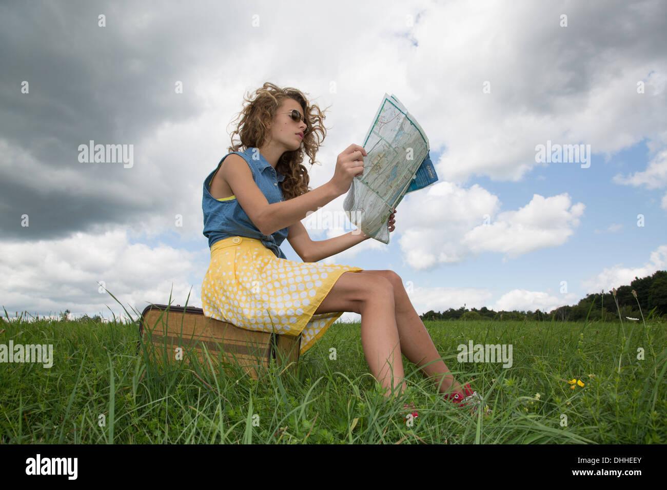 Teenage girl sitting on suitcase reading map - Stock Image