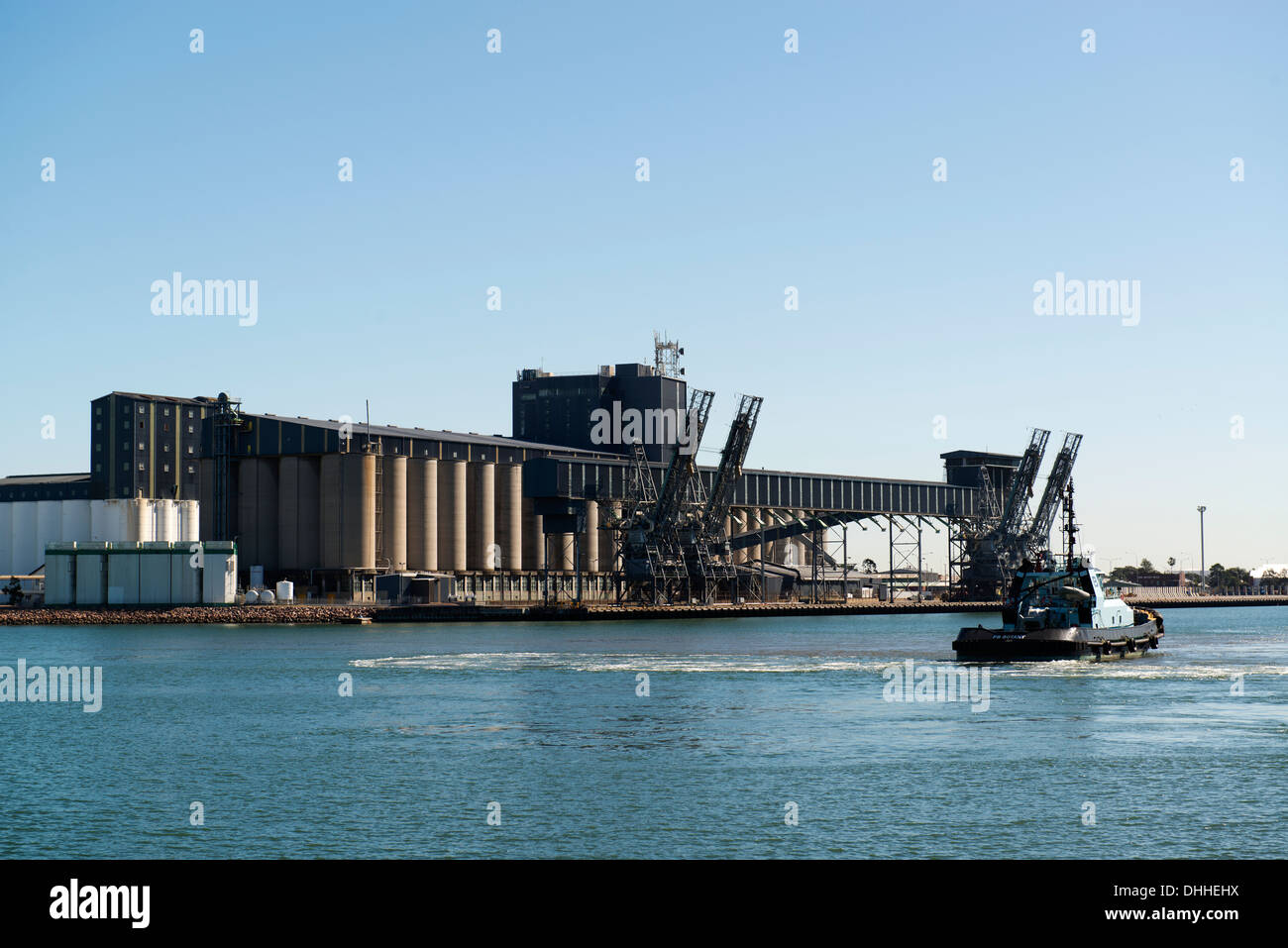 Tugboat and ship loading facilities on the Hunter River in Newcastle. - Stock Image
