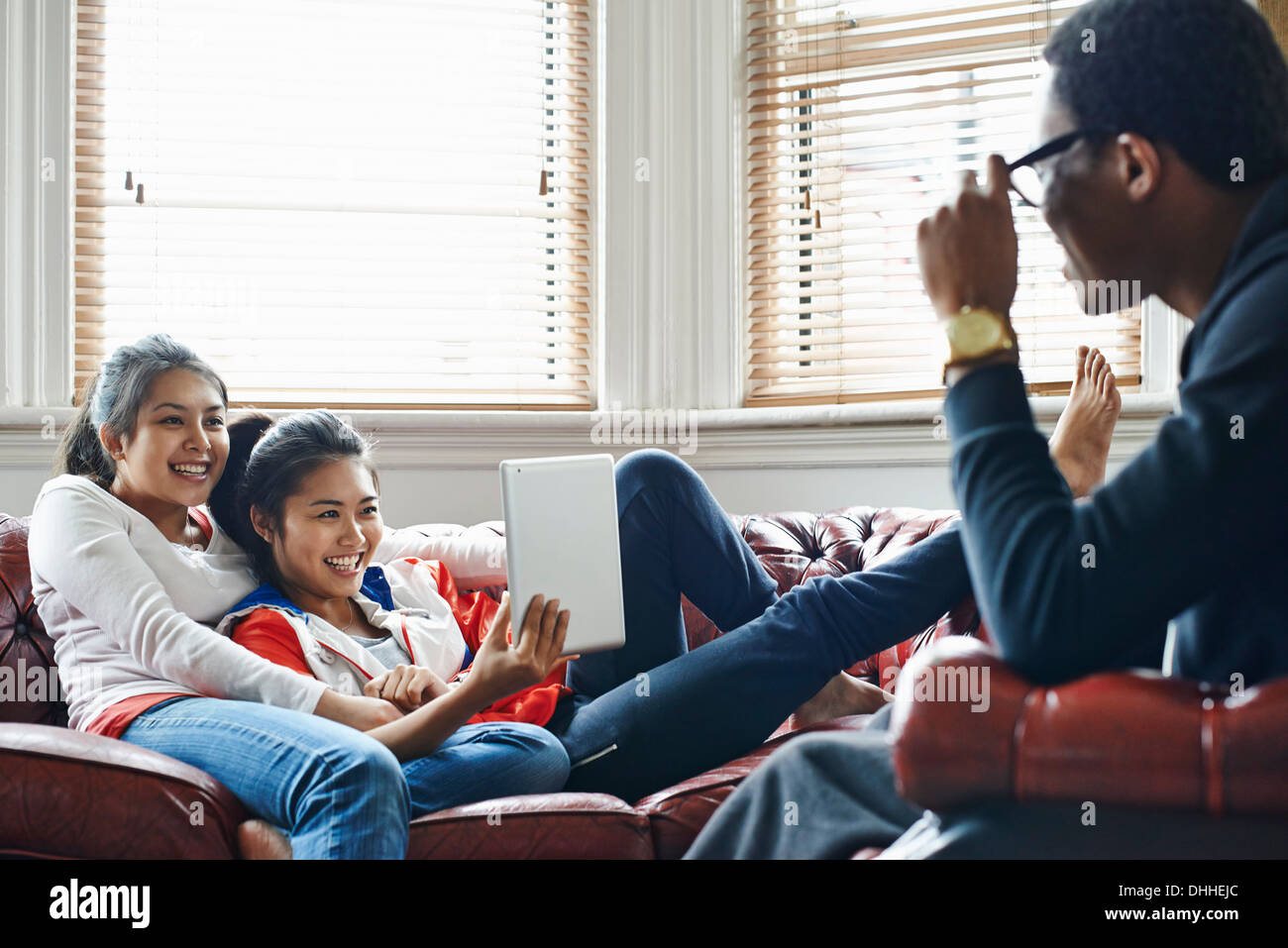 Three young adults in living room with digital tablet - Stock Image