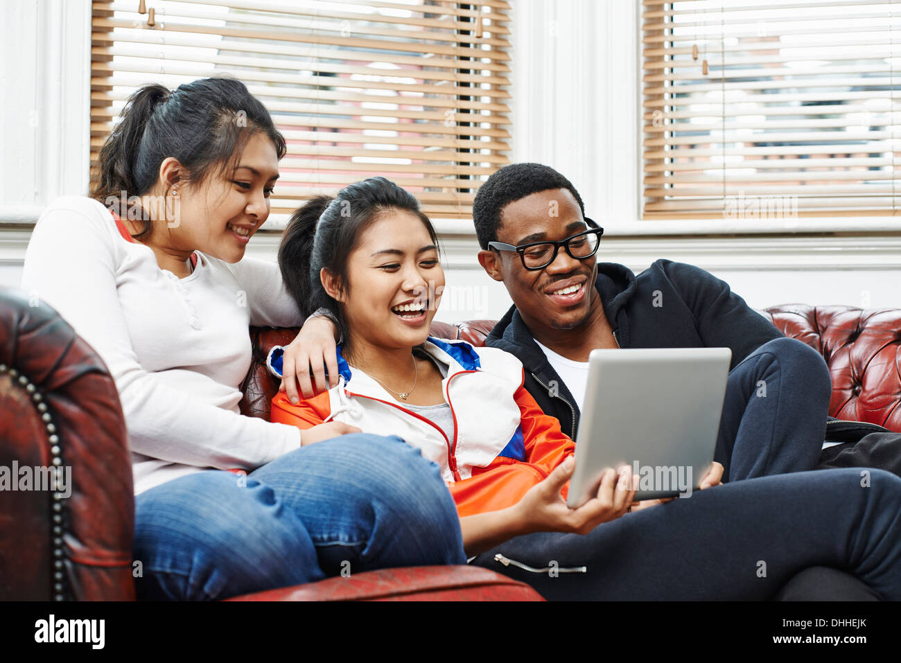Three young adults sitting on sofa looking at digital tablet - Stock Image