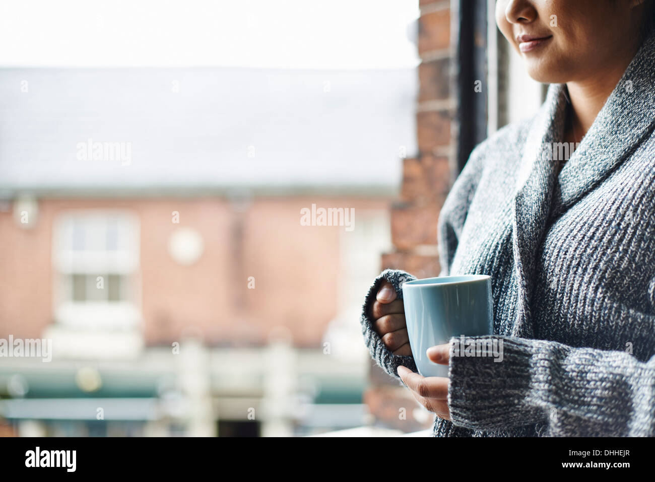 Young woman in kitchen holding mug of coffee - Stock Image