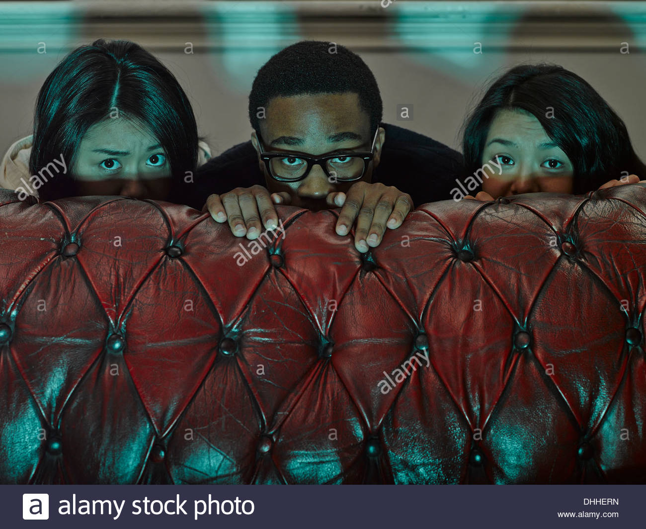 Three young adult friends hiding behind sofa - Stock Image
