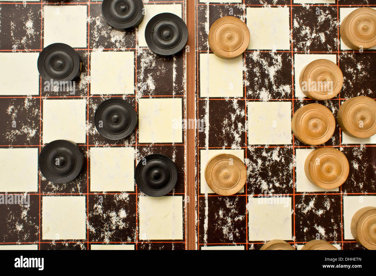 Draughts pieces and a board as a background image - Stock Image
