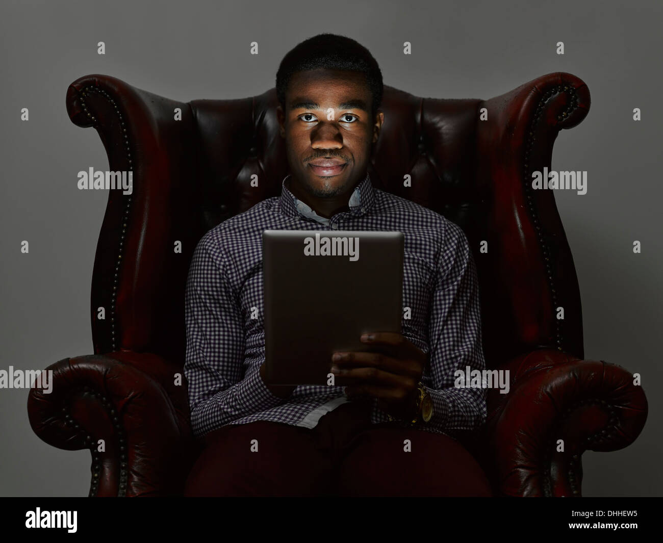 Portrait of sinister young man in armchair with digital tablet - Stock Image