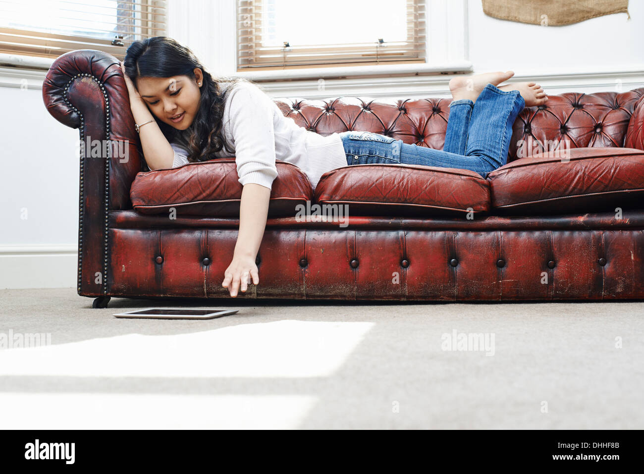 Young woman lying on sofa reaching for digital tablet - Stock Image