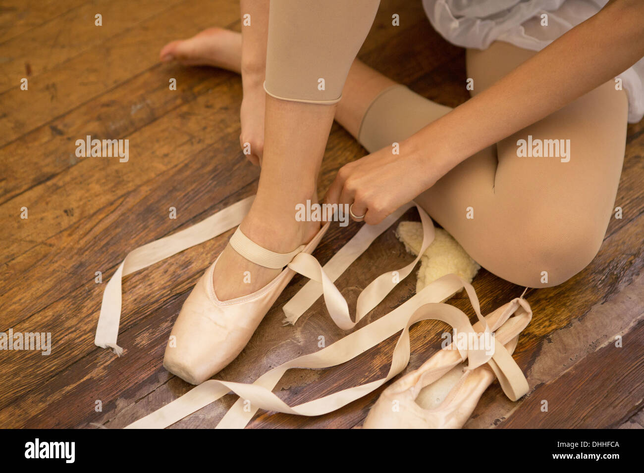 Ballet dancer tying shoe - Stock Image