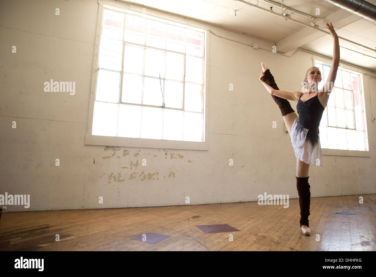 Ballet dancer on one leg in studio - Stock Image