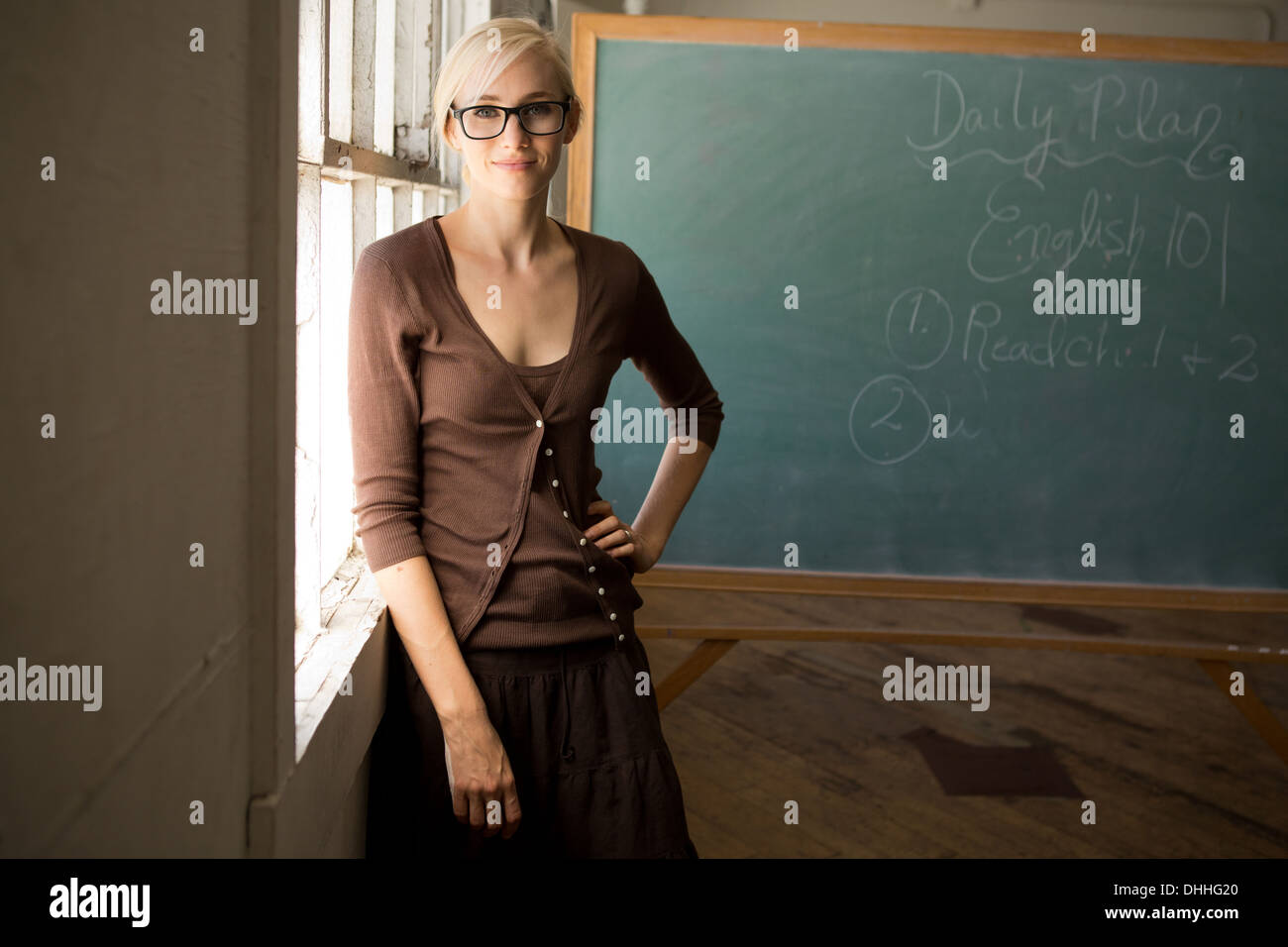 Portrait of teacher with hand on hip and blackboard - Stock Image