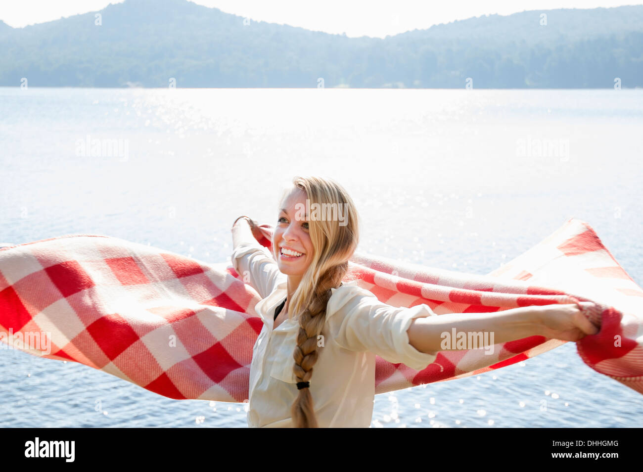 Young woman holding blanket by lake, Hadley, New York, USA - Stock Image