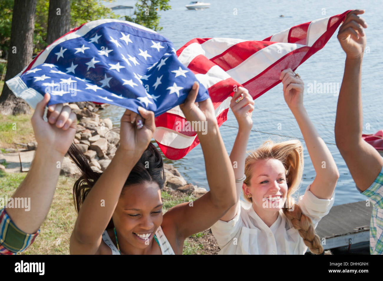 Friends holding US flag above heads, smiling - Stock Image