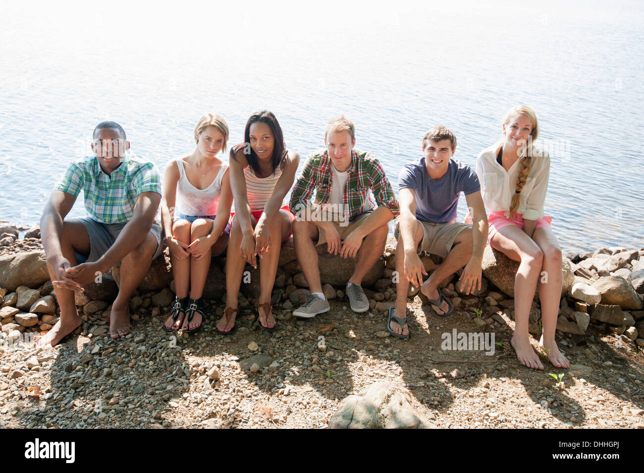 Portrait of friends sitting on stone wall - Stock Image