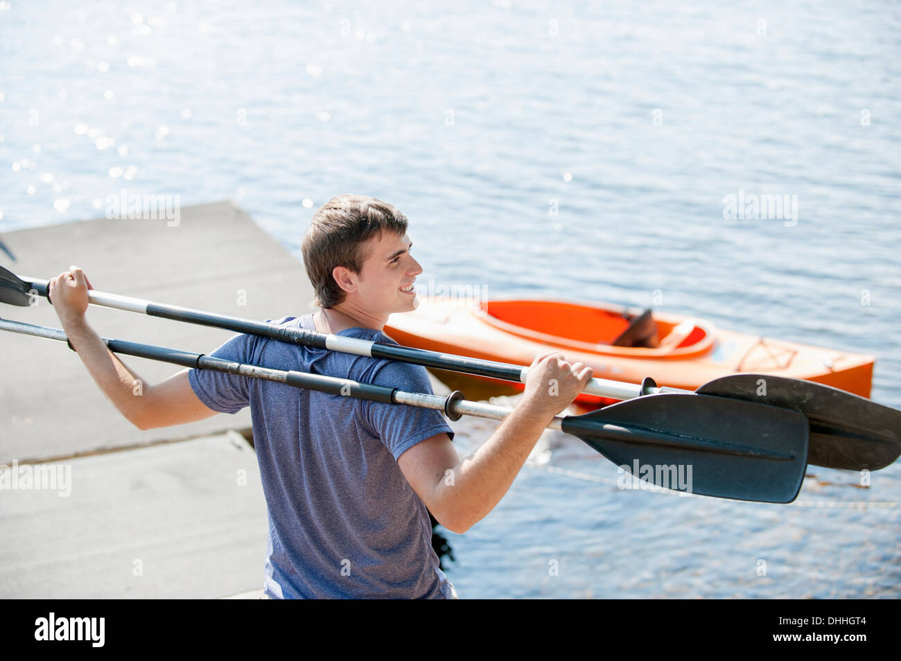 Young man holding canoe oars on shoulders - Stock Image