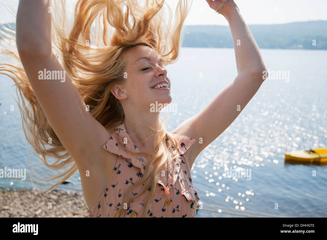 Portrait of young woman with long blonde hair and arms raised - Stock Image