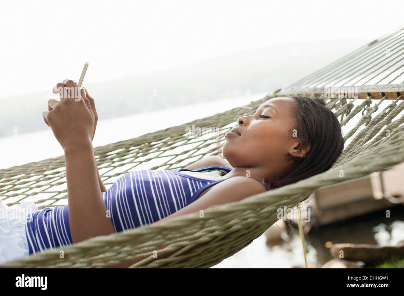 Young woman lying in hammock using cell phone - Stock Image