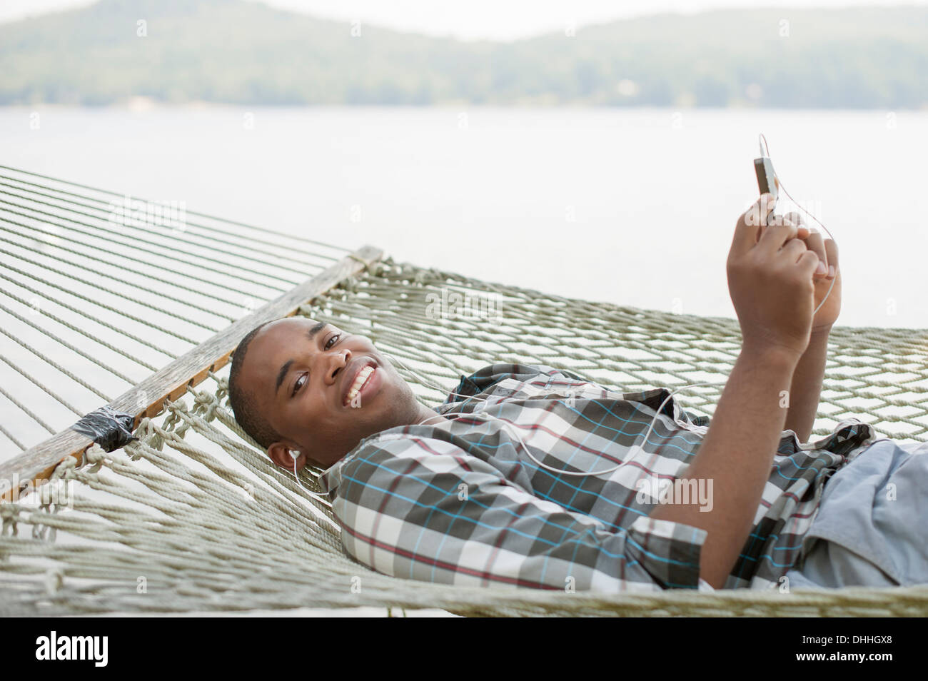 Young man lying on hammock listening to music - Stock Image