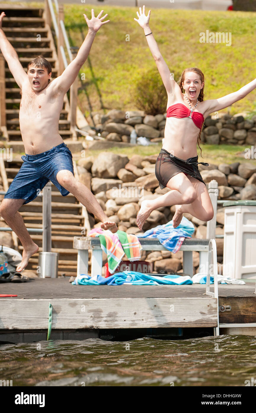 Young couple jumping into lake - Stock Image
