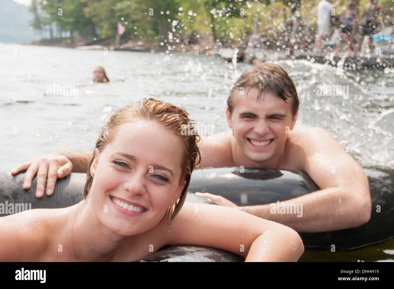 Young couple floating in inflatable rings - Stock Image