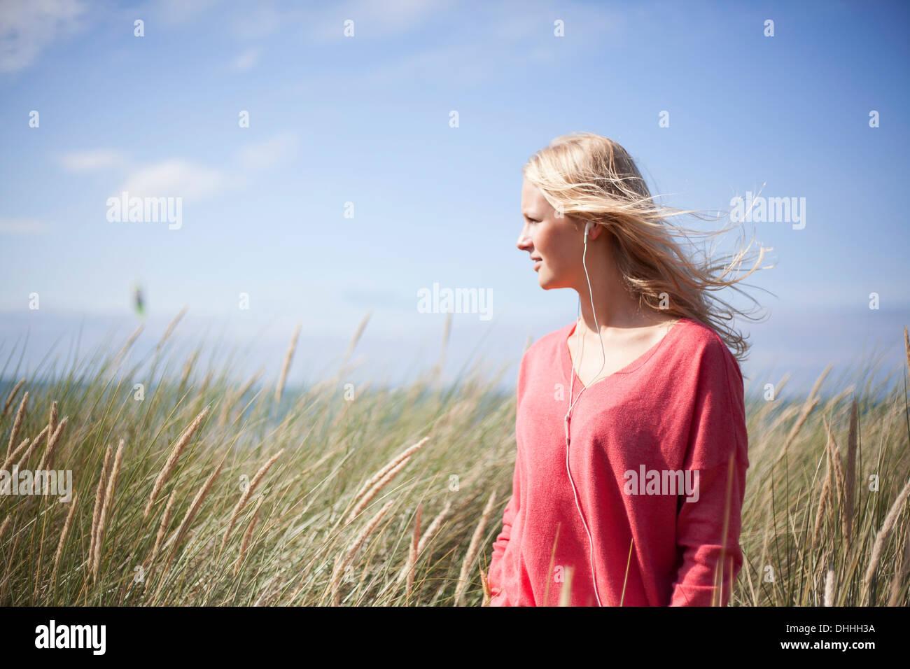 Portrait of blonde woman wearing pink sweater in marram grass, Wales, UK - Stock Image