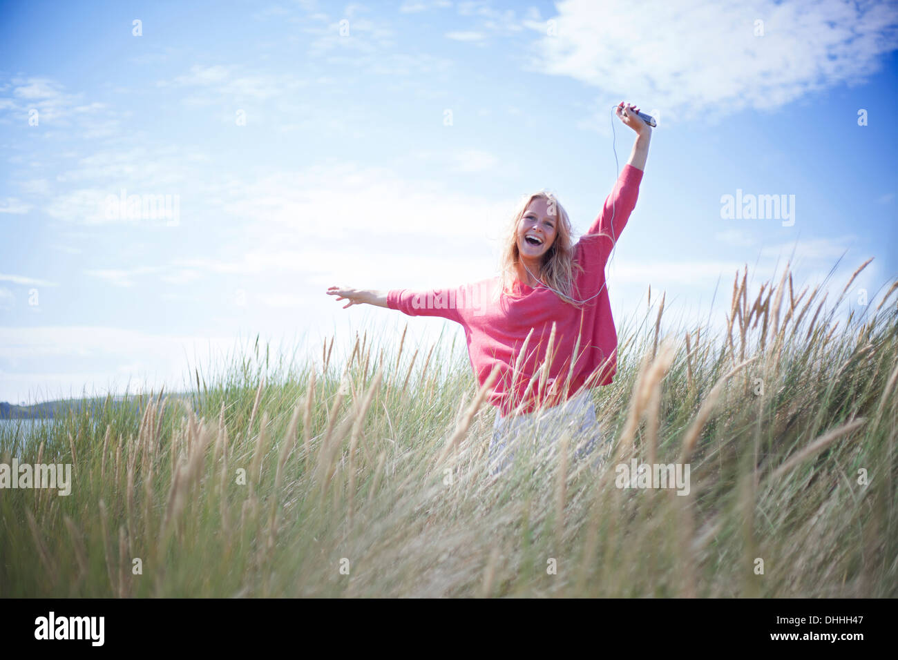 Portrait of woman dancing in marram grass, Wales, UK - Stock Image