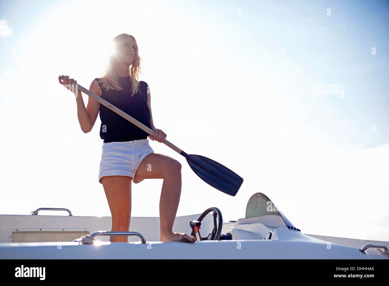 Woman standing holding oar on yacht, Wales, UK - Stock Image
