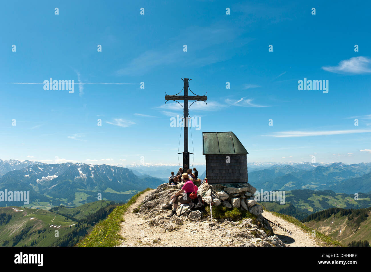 Mountain climber at the summit cross with a small chapel on Geigelstein Mountain, 1808 m, Geigelstein Nature Reserve - Stock Image