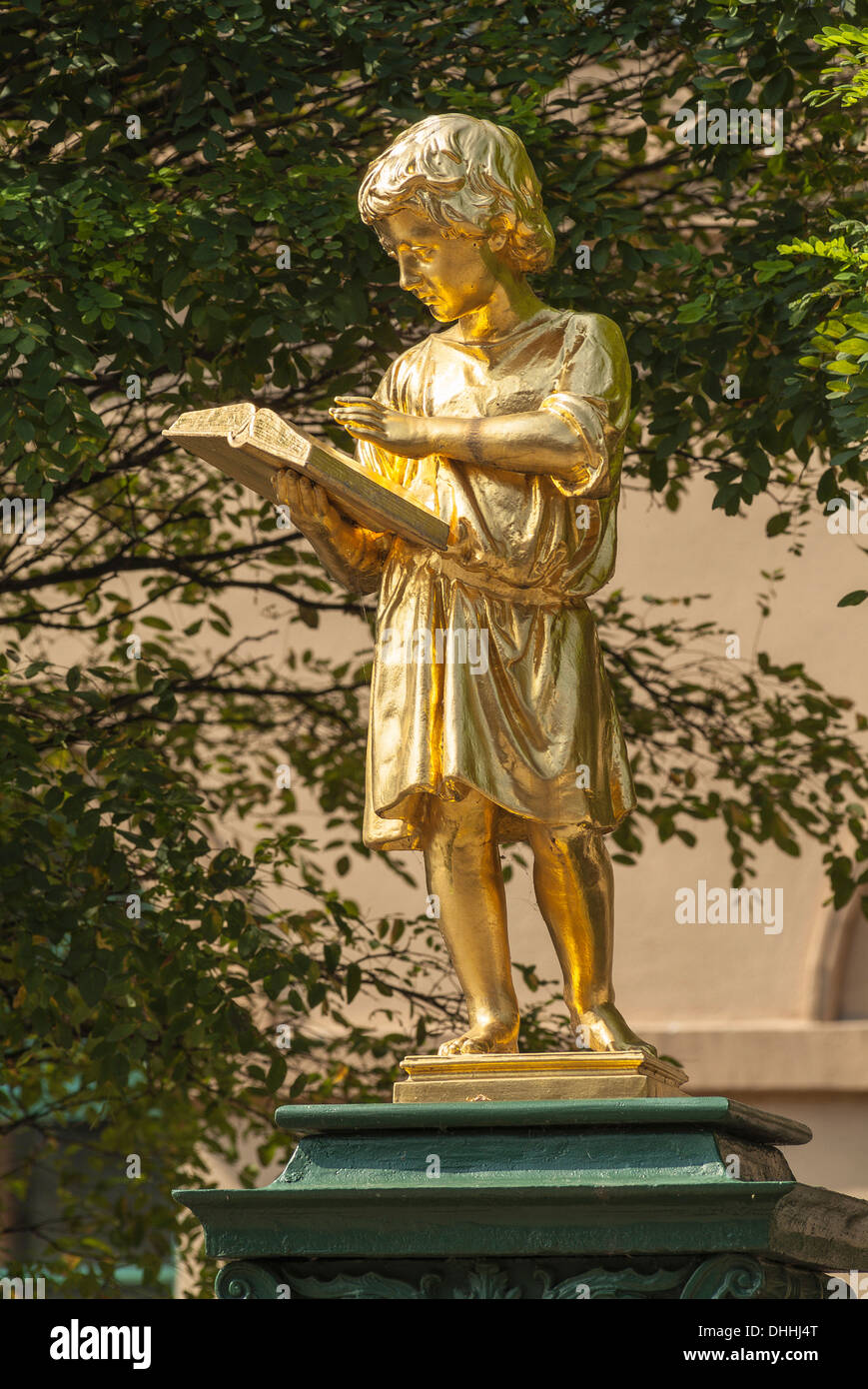 Gold plated fountain sculpture 'Boy Reading' in front of the former secondary school, now a music school, Weimar, Thuringia - Stock Image