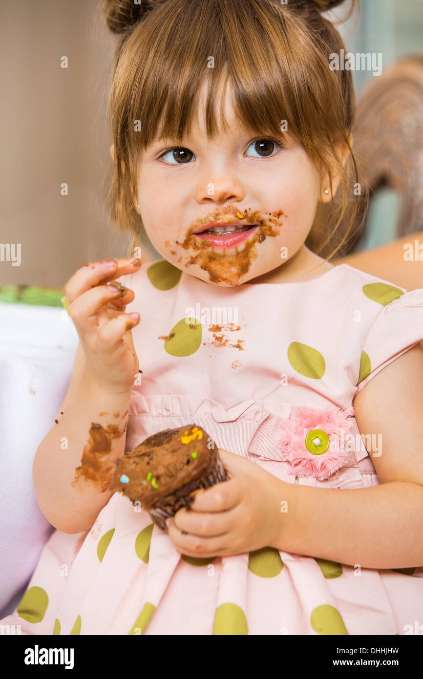 Girl Eating Birthday Cake With Icing On Her Face - Stock Image