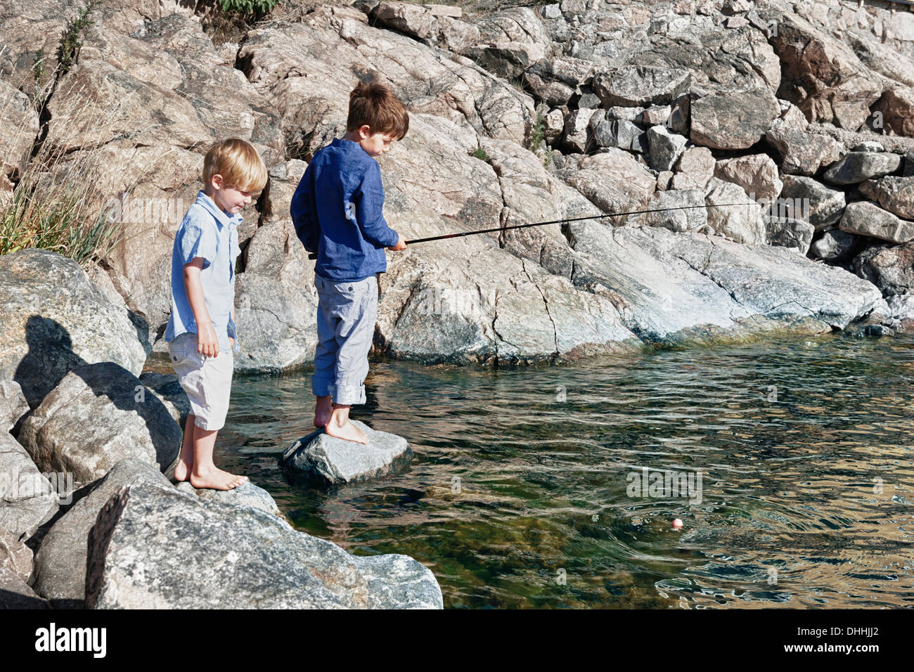 Two boys standing on rocks fishing, Utvalnas, Sweden - Stock Image