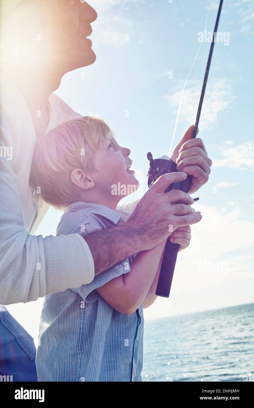Grandfather and grandson holding fishing rod, Utvalnas, Sweden - Stock Image