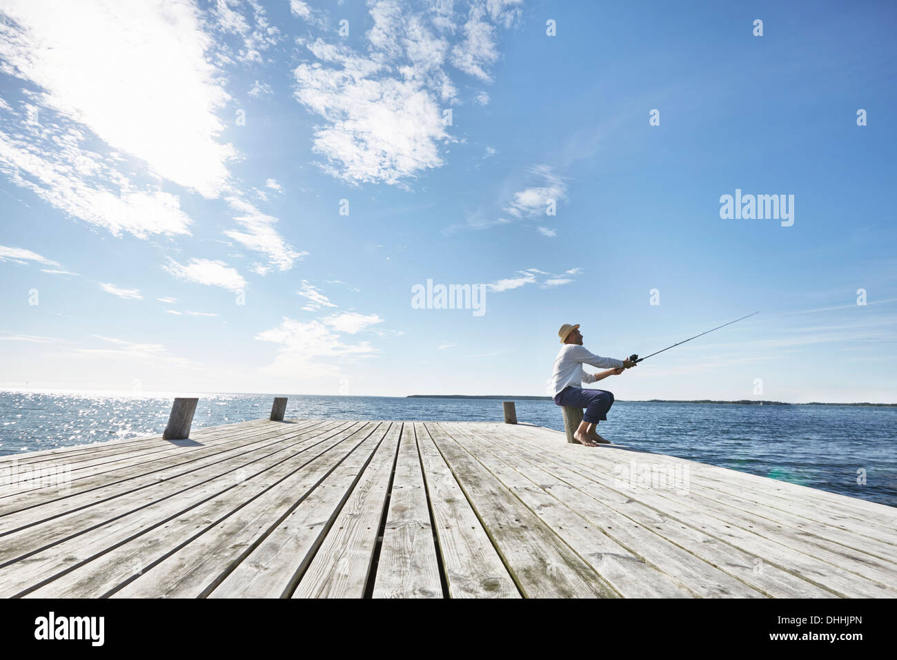 Mid adult man fishing off pier, Utvalnas, Sweden - Stock Image