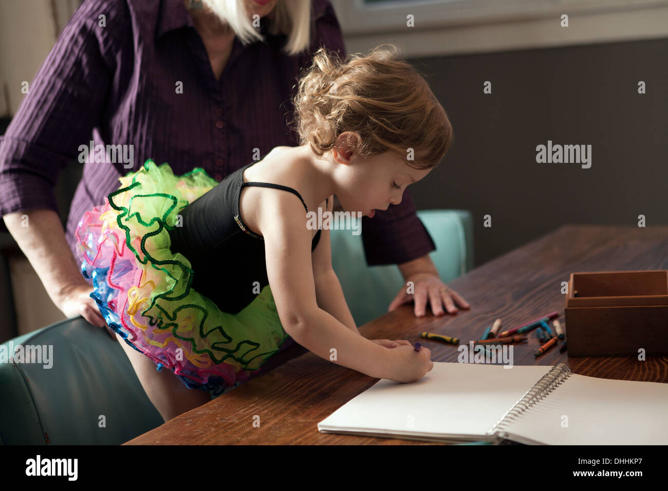 Grandmother and granddaughter standing at table drawing - Stock Image