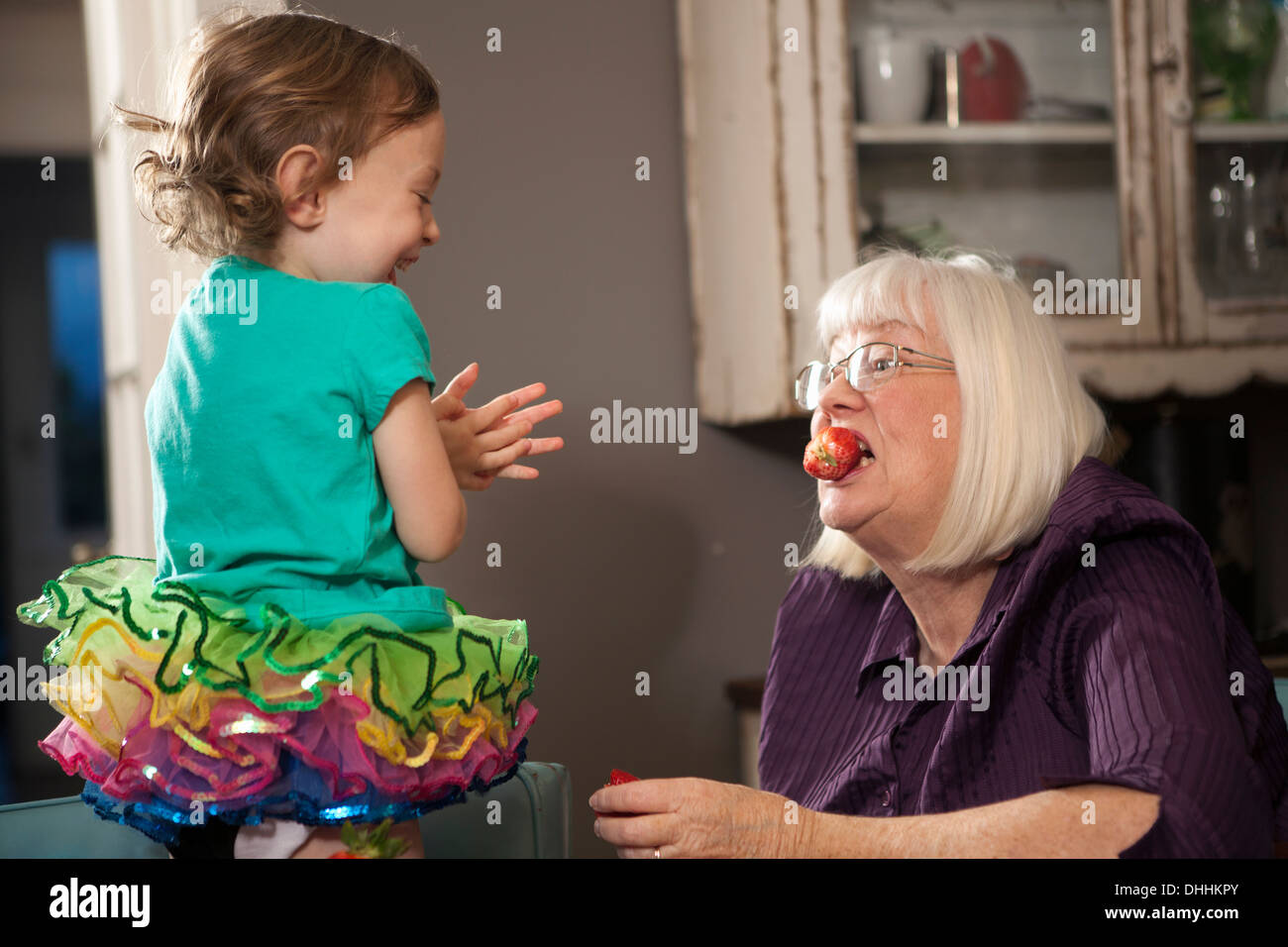 Girl feeding grandmother a strawberry - Stock Image