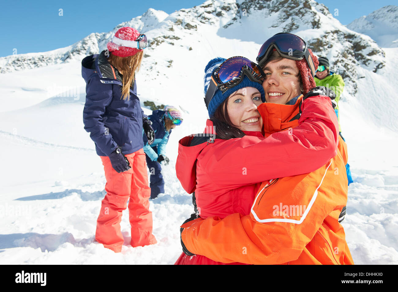 Friends wearing skiwear hugging, Kuhtai, Austria - Stock Image
