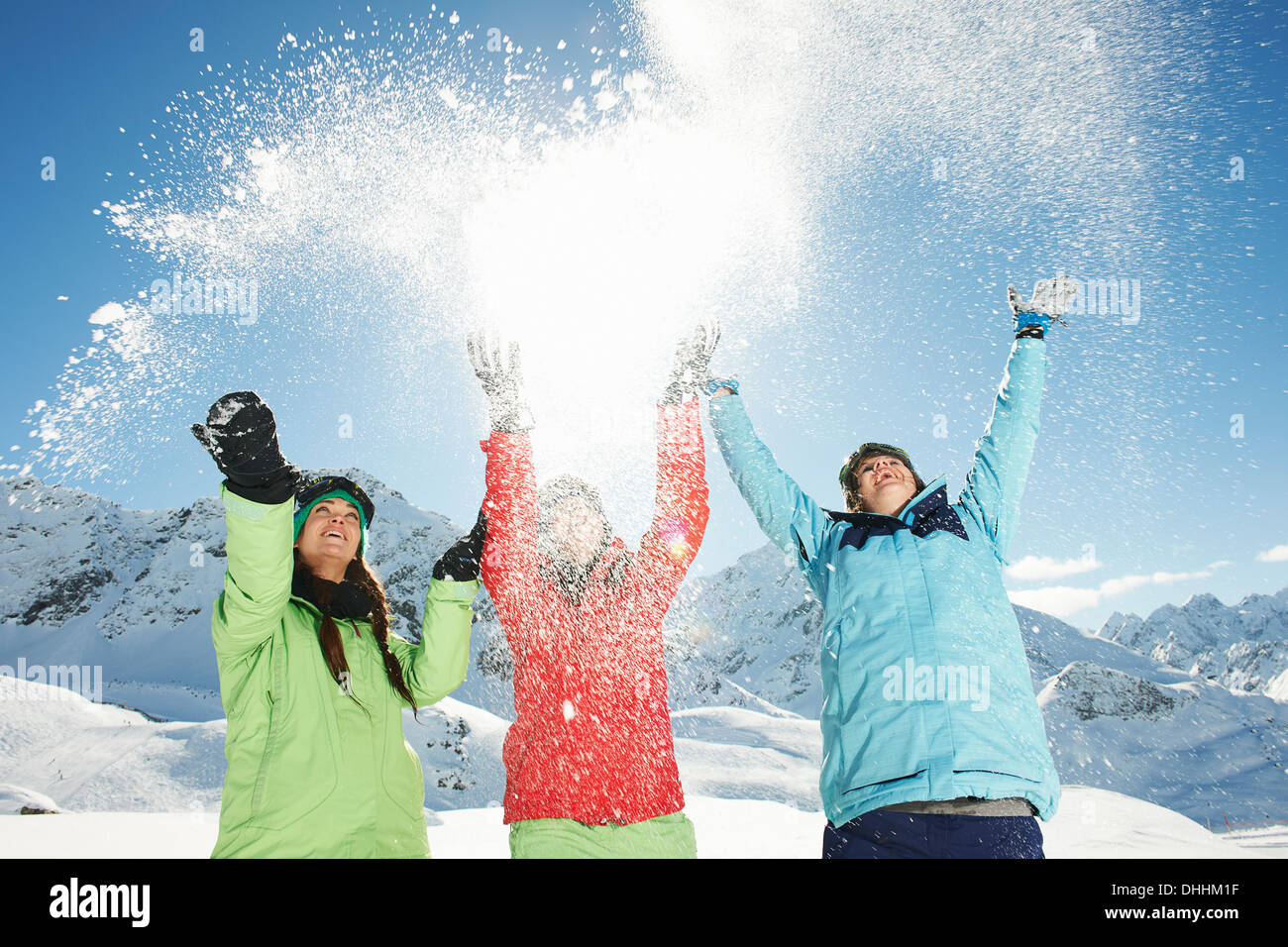 Female friends throwing snow mid air, Kuhtai, Austria - Stock Image