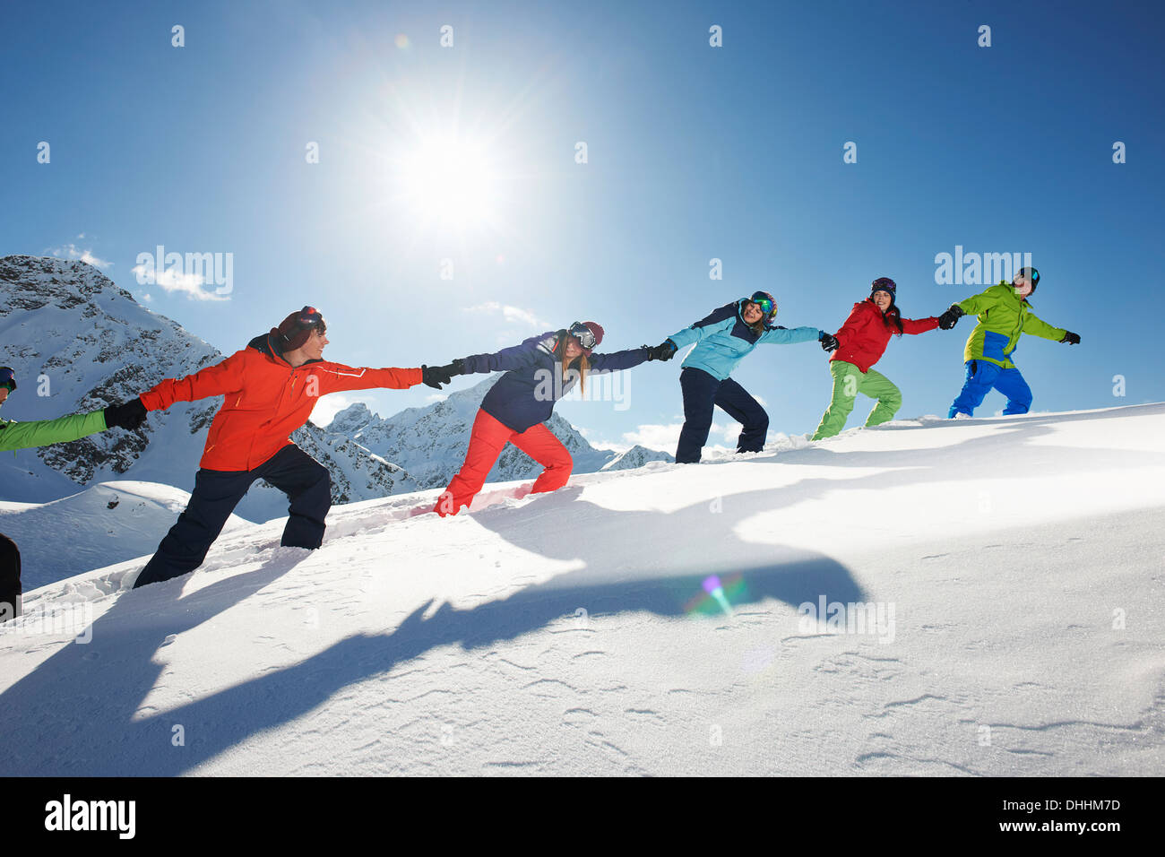 Friends pulling each other uphill in snow, Kuhtai, Austria - Stock Image