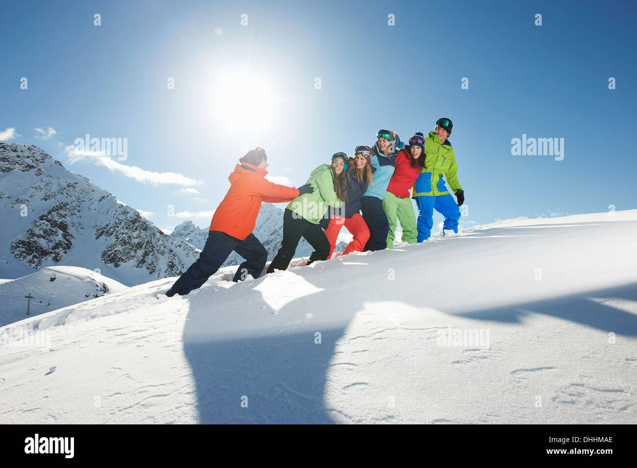 Man pushing friends uphill in snow, Kuhtai, Austria - Stock Image